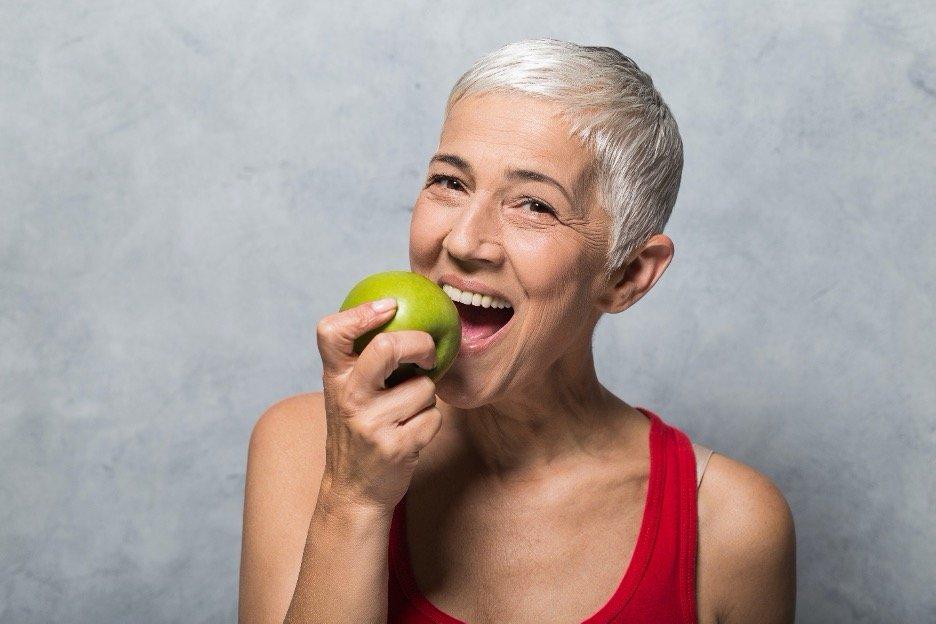 older adult eating an apple