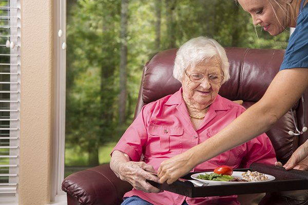 Caregiver serving lunch to senior woman