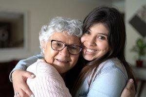 caregiver hugging senior with dementia symptoms